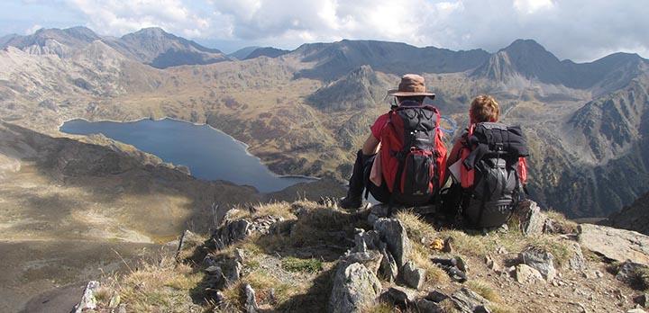 Två personer som blickar ut över Pyreneerna med vandringsutrustning.