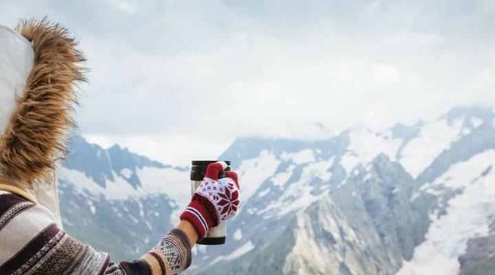 Person håller i en termos framför berg.
