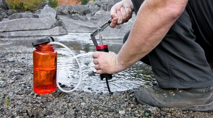 Person använder ett vattenfilter att filtrera vattnet med.