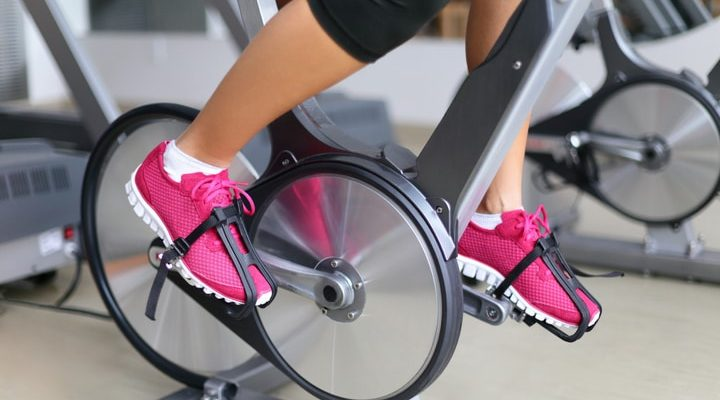 En person med rosa spinningskor som cyklar på en spinningcykel.