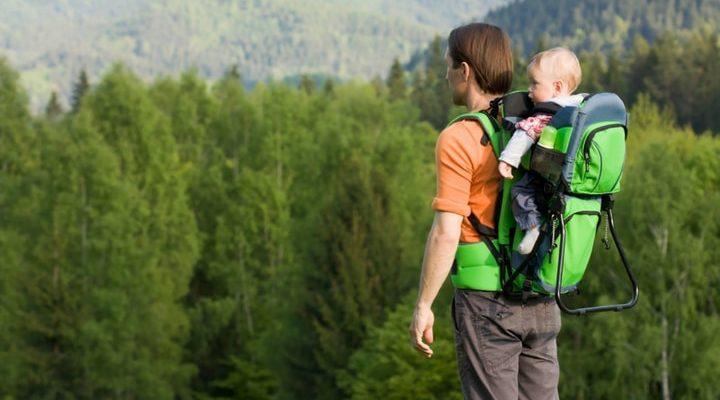 Pappa med barn i en bärstol på ryggen.