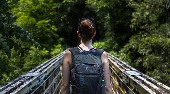Kvinna som går med ryggsäck i skogen.