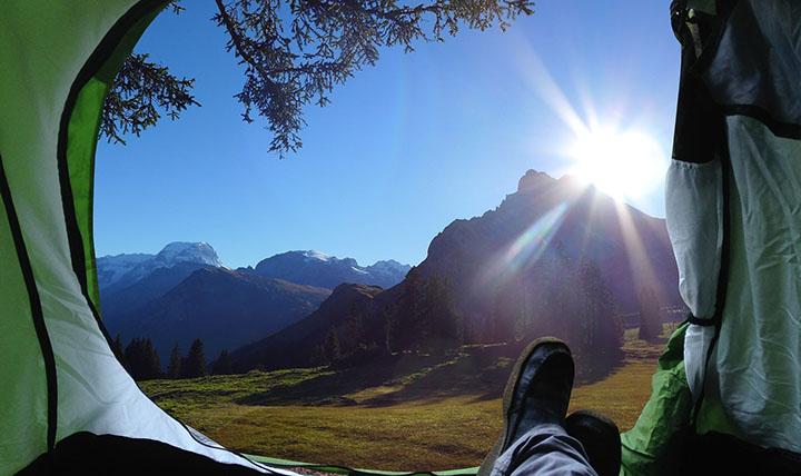 En person vars fötter man ser i ett tält, och den vackra utsikten utanför.