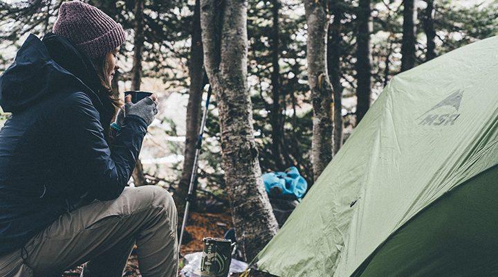 En person som sitter vid ett tält ute i naturen.