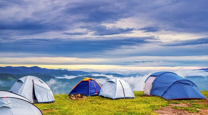 Flera tält som är uppsatta bredvid varandra uppe på en kulle.