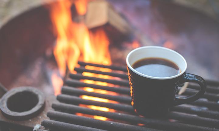 En kaffekopp som står på ett galler vid en brasa.