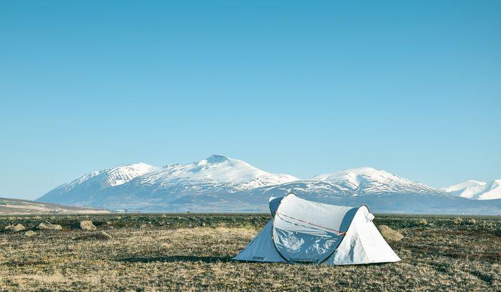 En ljusblått tält som är uppstält framför flera berg.