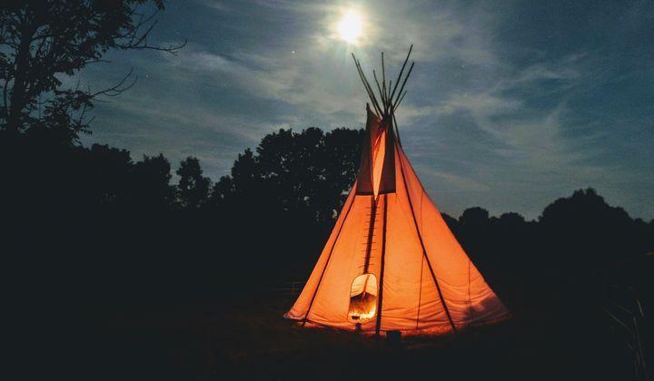 Ett orange tält som står ute i naturen på kvällen.