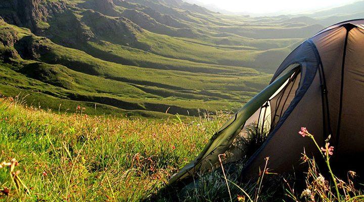 Ett campingtält ute i gräset framför en vacker grönskande natur.