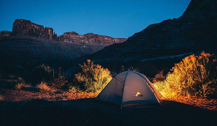 Ett tält som står uppsatt på kvällen i naturen.