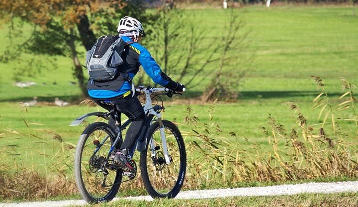 En person som cyklar på en mountainbike med cykelhjälm och cykeljacka.
