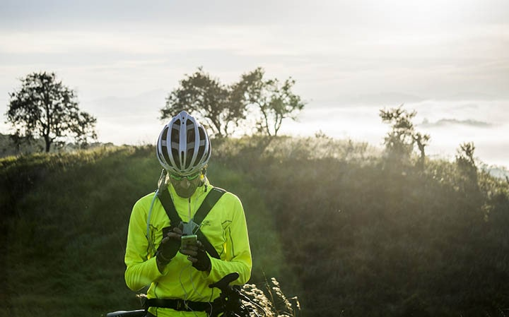 Man med cykeljacka och cykelhjälm ute i naturen.