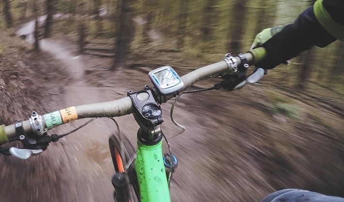 Cykeldator som sitter på styret på en cykel som åker snabbt ner för en backa i skogen.