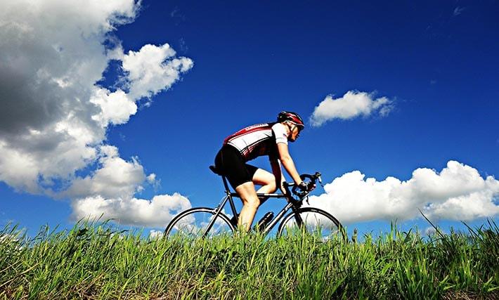 En man som cyklar i solen med en cykelhjälm på huvudet.