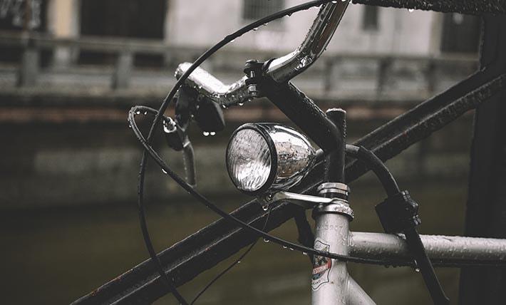 En cykellampa som sitter fast på en cykel. Cykeln och lampan är blöt från regnet.