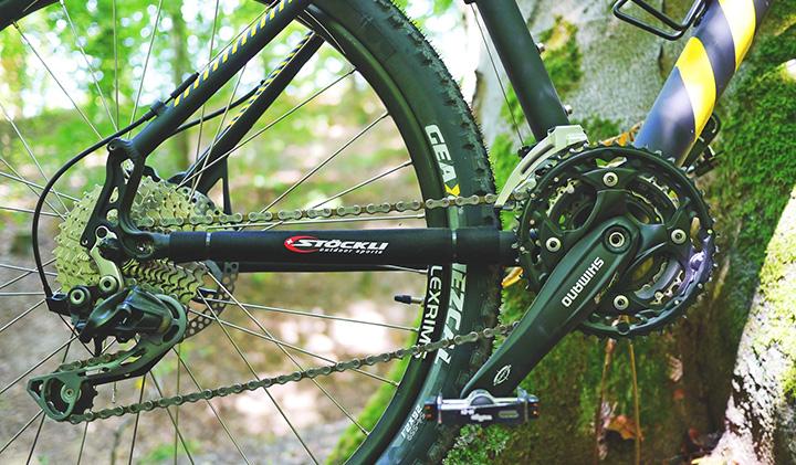 En cykel i skogen, där det är fokus på cykelpedalen.