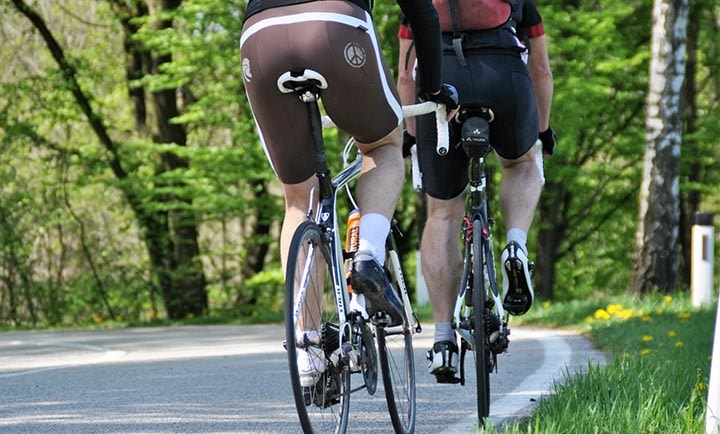 Två cyklister som cyklar vid en landsväg. Båda sitter på moderna och kvalitativa sadlar.