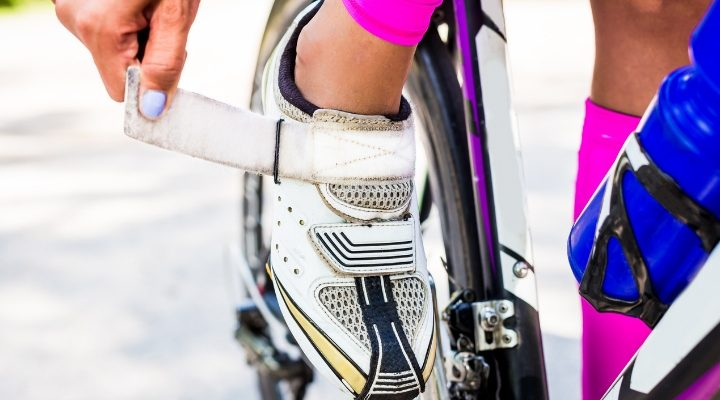 En person på cykel som knäpper sin cykelsko.