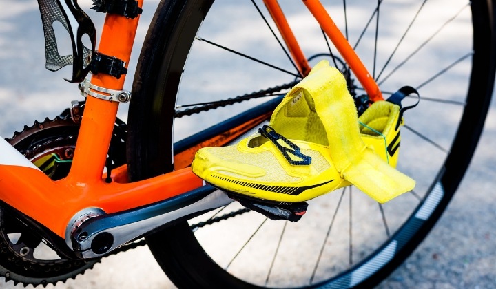 En gul cykelsko som sitter fast på en pedal.