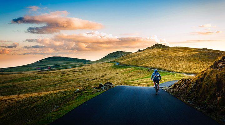 En väg genom ett landskap, en cyklist på vägen.