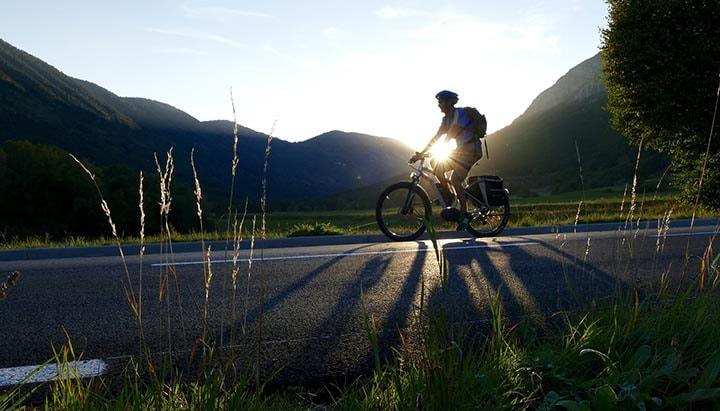 En man som cyklar på en elcykel i solnedgången.