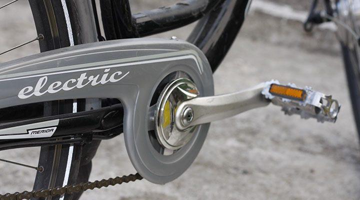 Pedaler på en hybridcykel som är grå.