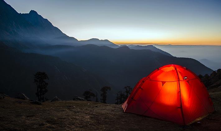 Ett tält som står uppe på ett berg där solen precis gått ner.