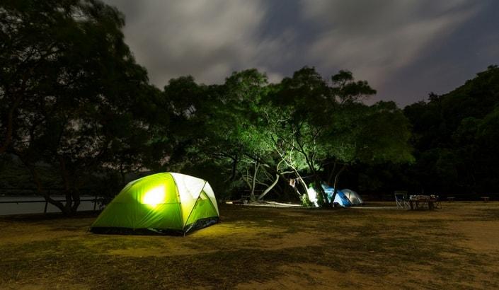 Tält som lyser upp vid i campingplats på kvällen.