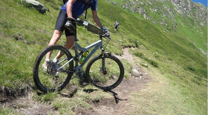En person ute i naturen med en mountainbike-cykel, det sitter en flaskhållare på cykeln.