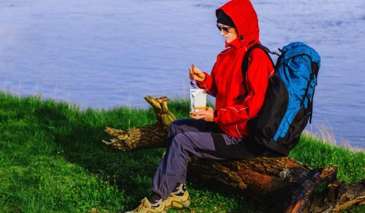 En person som sitter utomhus på ett träd och äter frystorkad mat.