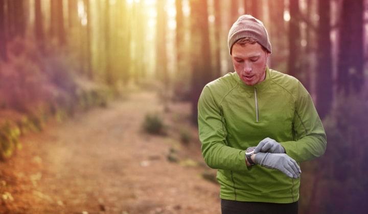 Man som är ute på löprunda i skogen med gps-klocka.