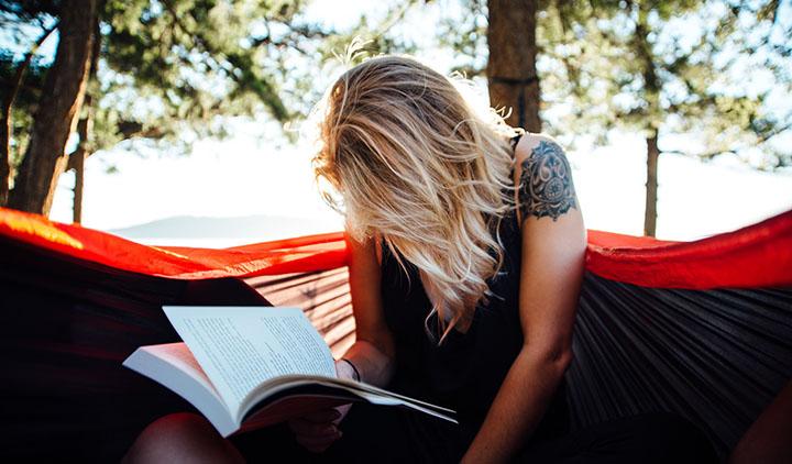 En tjej sitter i en hammock i skogen och läser en bok.