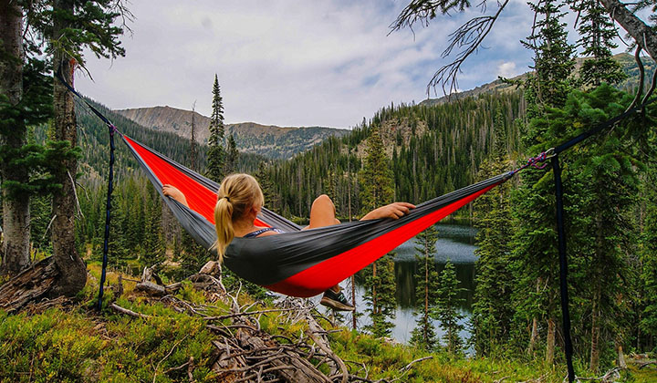 En kvinna som ligger i en hammock i skogen.