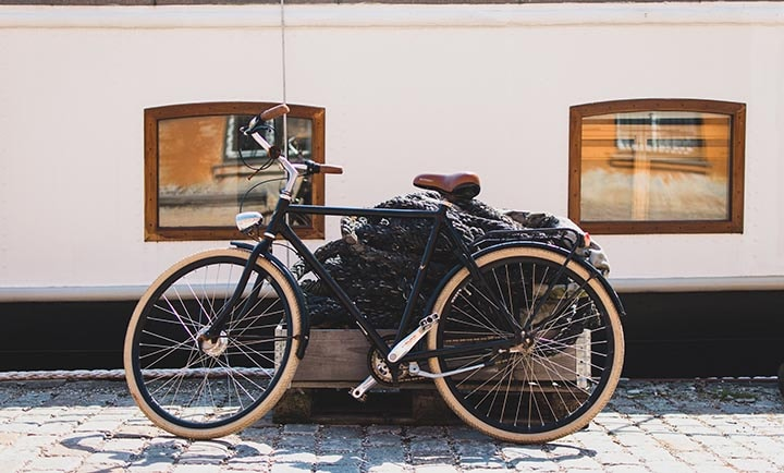 En cykel som står lutad med en låda med stora rep i.