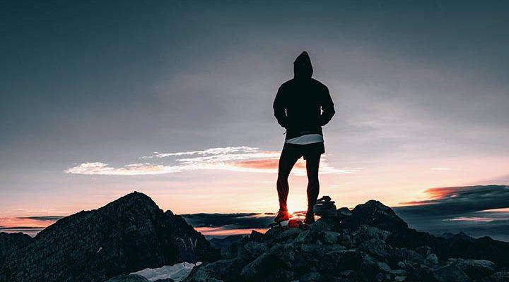 En person står uppe på ett berg framför en solnedgång.
