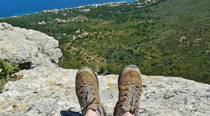 Person sitter uppe på ett berg i vandringsskor.
