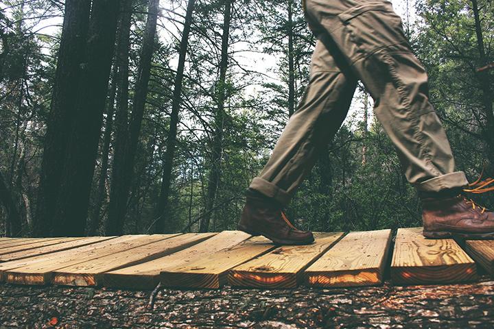 Person går på en stig i skogen i vandringsskor.