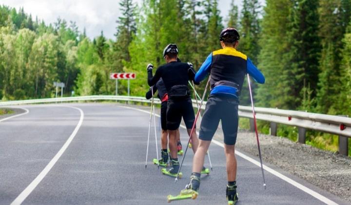 Tre personer som åker rullskidor på en asfalterad väg.