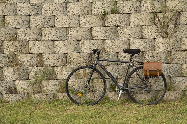 En hybridcykel som står mot en stenvägg.
