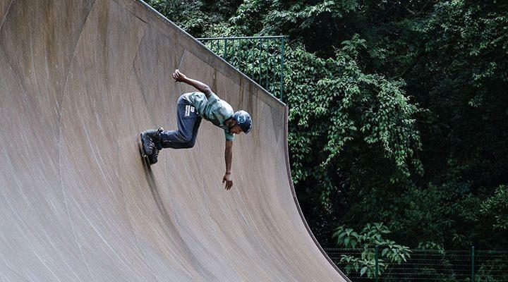 En kille med inlines som åker i en skate-ramp.