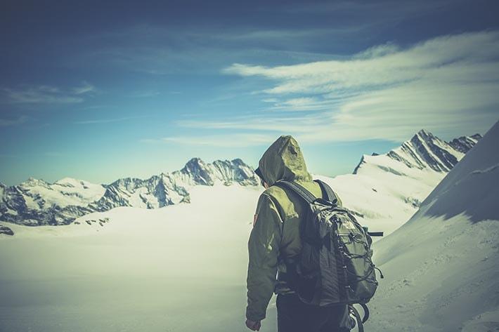 En person som står uppe på ett berg med en shell-jacka på sig.
