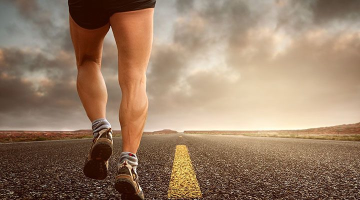 Joggares ben som springer på en väg.