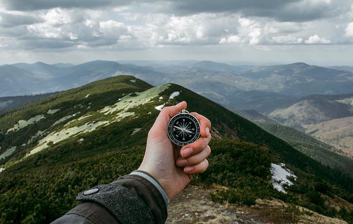 En hand som håller i en kompass med massa berg i bakgrunden.