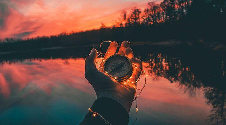 En solnedgång och en person som håller i en kompass.