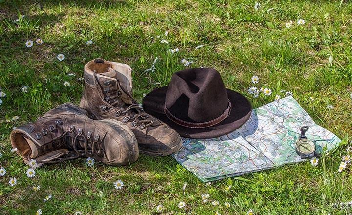 Ett par kängor, en hatt, en karta och en kompass som ligger i gräset.