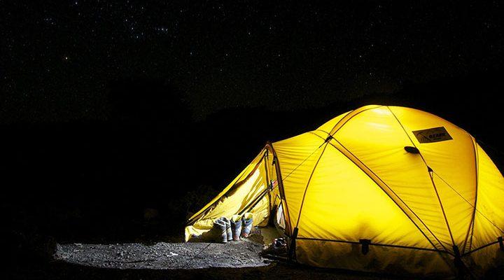 Ett gult upplyst kupoltält i mörkret.