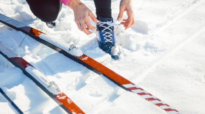 En person som tar på sig längdpjäxor bredvid sina längdskidor.