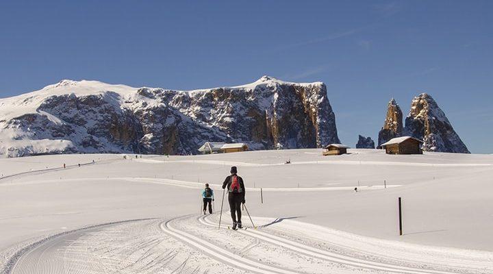 Två längdskidåkare framför ett stort berg och några stugor.