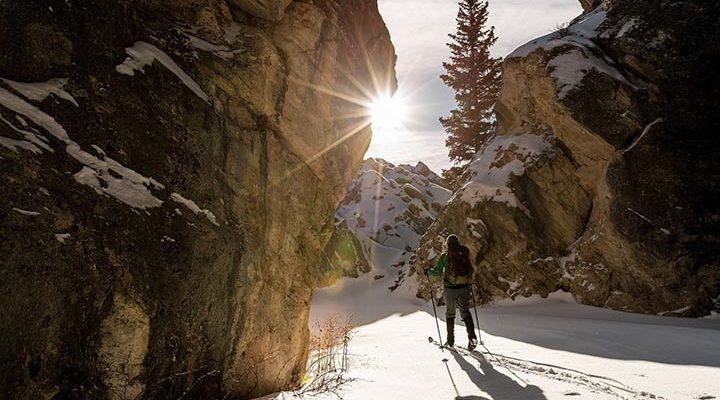 En person som åker längdskidor mellan två berg.