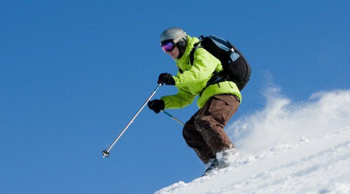 En skidåkare som åker off pist med en lavinrycksäck på sig.